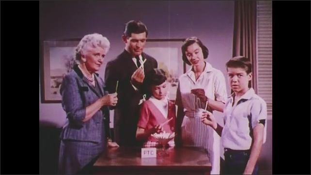 1960s: UNITED STATES: family take PTC strip. Lady puts paper strip in mouth. Man tastes bitter strip. Three generations of family take test.