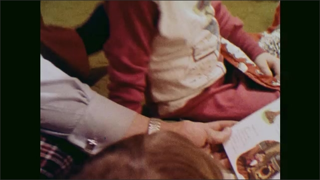 1970s: UNITED STATES: man reads book with children at home. Picture book in man's hands. Parents read book with child.