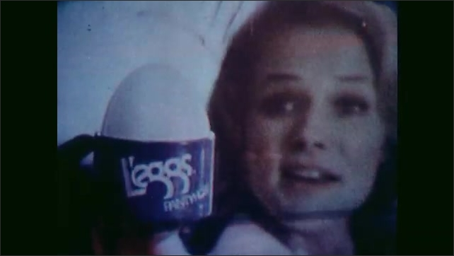 1970s: UNITED STATES: children watch commercials on television. Lady in shoes and pantyhose. Traditional woman role on television. L'eggs advert.