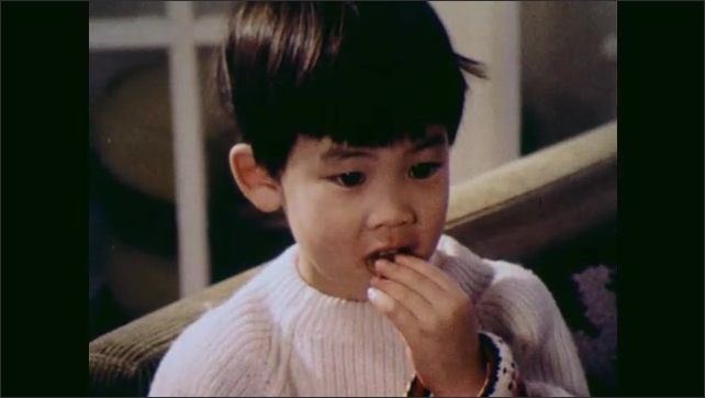1970s: UNITED STATES: children watch commercials on television. Boy eats sweets in front of television.