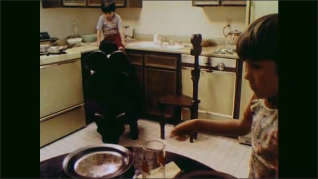 1970s: UNITED STATES: spoon stirs spaghetti in pan. Children prepare dinner with father at home. Boy lays table. Boy stands by stove.