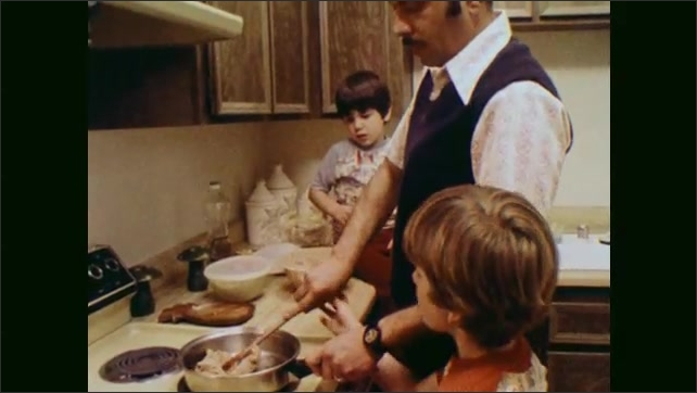 1970s: UNITED STATES: children help father cook food in kitchen. Boy stirs pan.