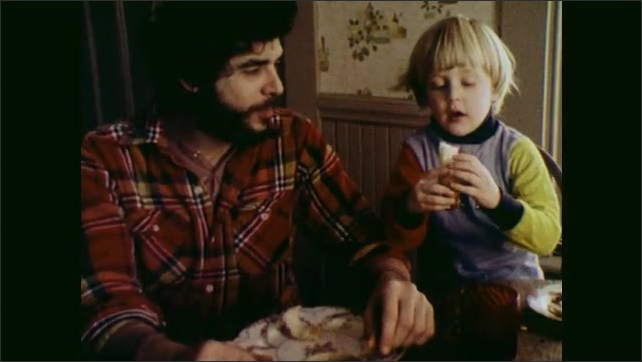 1970s: UNITED STATES: boy eats tangerine with father at home. Man eats apple from plate