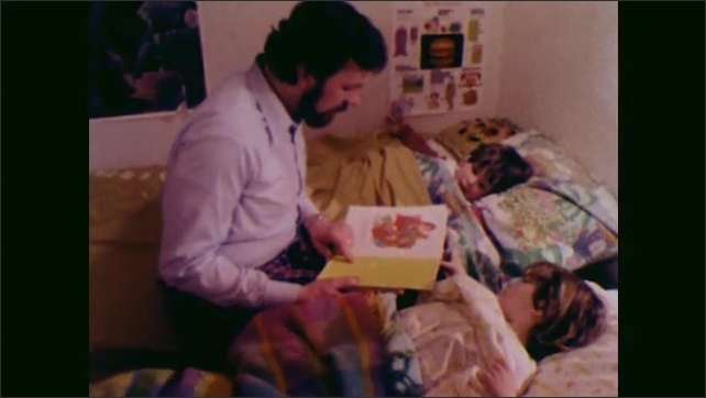 1970s: UNITED STATES: boy listens to story at bedtime. Man reads to children at bedtime.