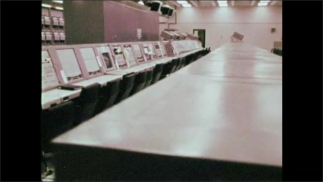 1960s: Rows of computer panels in control room. Steel girders at outdoor stadium. Crowds of people gather at stadium and field to watch rocket launch.