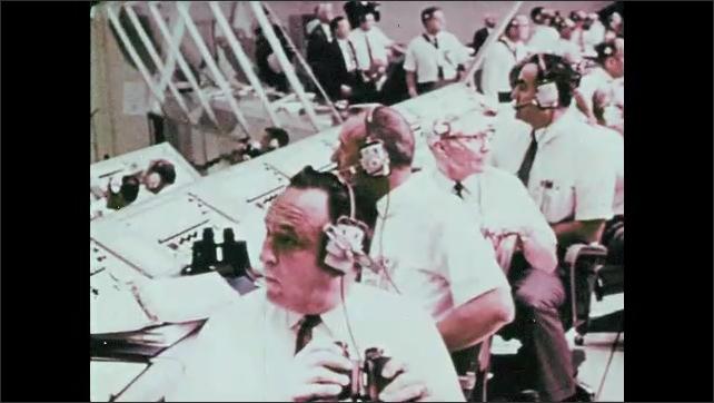 1960s: Men wear headsets and speak on phones in control room. Engineer looks through binoculars. Rocket stands at tower. Crowd stands in stadium.