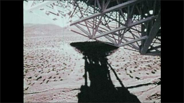 1960s: Satellite dish in desert. Earth.