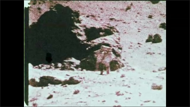 1960s: Astronauts walk towards boulder on the surface of the moon.