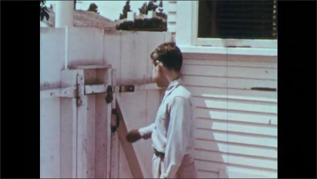 1950s: Boy walks through gate door and looks at dogs barking in cages. Boy leaves City Dog Pound and looks around.