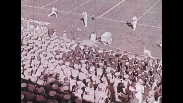 1930s: Band marches over football field. Sports announcer at microphone. Cheerleaders excite crowd. Players run over field, tackle.