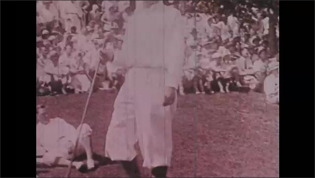 1930s: Man with radio equipment announces into microphone. Golfer swings before crowd. Man hands club to another man. Golfers and spectators walk on course. Man places club to golf ball.