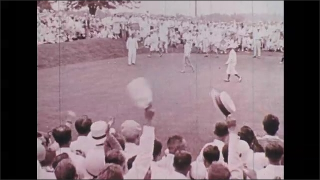1930s: Man puts golf ball into hole, crowd cheers, men walk across course. Car with flags, motorcycles parade through clapping street crowd.