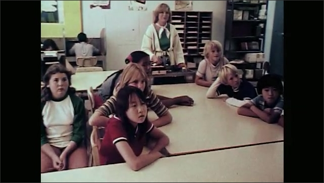 1970s: Classroom.  Teacher uses film projector.  Words appear on screen.  Students watch and speak.