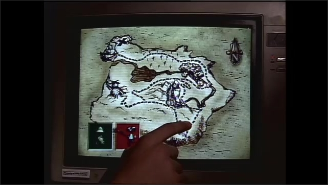 1990s: UNITED STATES: girl and boy do treasure hunt on computer. Finger points to path. Hands on computer keys.