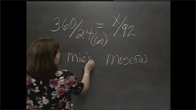 1990s: UNITED STATES: lady writes on chalkboard. Boy in classroom. Longitude and latitude, Moscow written on board.