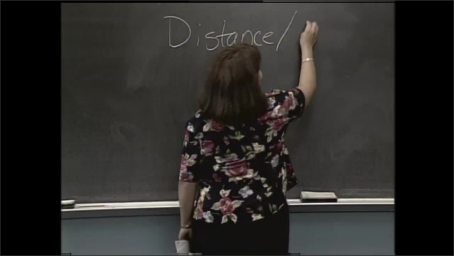 1990s: UNITED STATES: teacher smiles at student. Girl smiles at boy. Distance divided by time equation on chalk board.