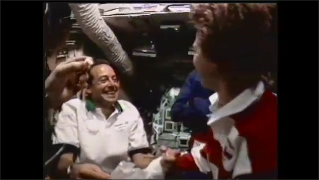 1990s: UNITED STATES: astronauts meet up in space on shuttle. Astronaut enters through hatch. Astronauts hug.