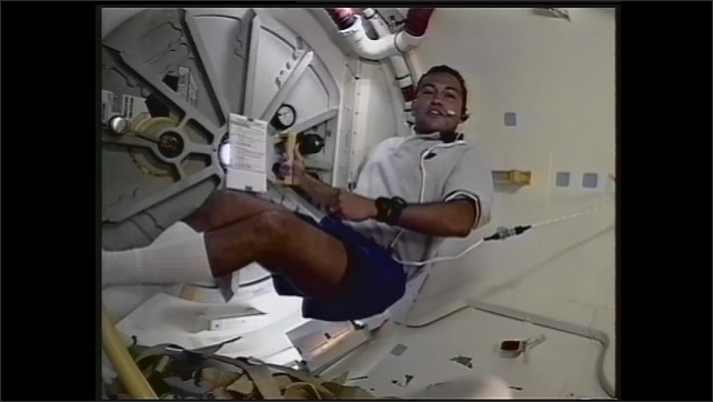 1990s: UNITED STATES: man at petrol pump. Astronaut in space floats by hatch. Russian space station MIRA visit.