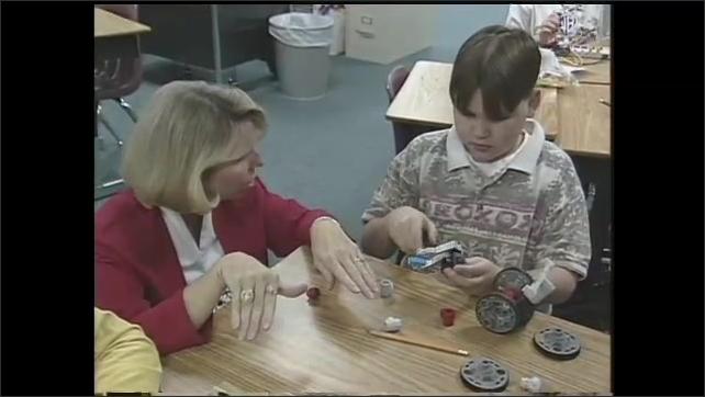 1990s: UNITED STATES: teacher talks to boy at desk. Boy builds robot. Students test robots.
