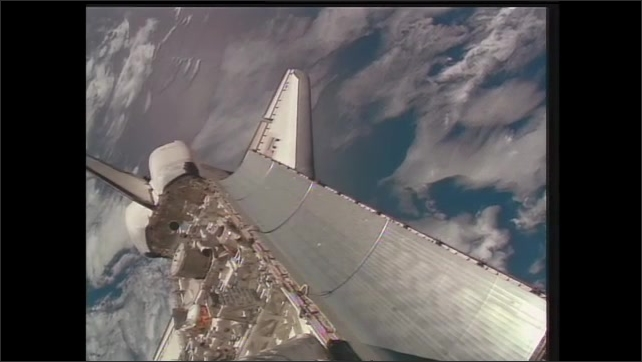1990s: UNITED STATES: exterior view of space shuttle in space. Female astronaut looks at camera.