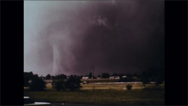 1970s: Man looks out window. Man listens to radio. Woman carries child down steps. Tornado spins in field. Woman opens windows.