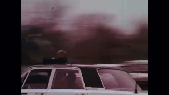 1970s: House in ruins. Women hug. Police car speeds down street. Emergency services vehicles drive down street. Man and woman look out door, woman is shocked.