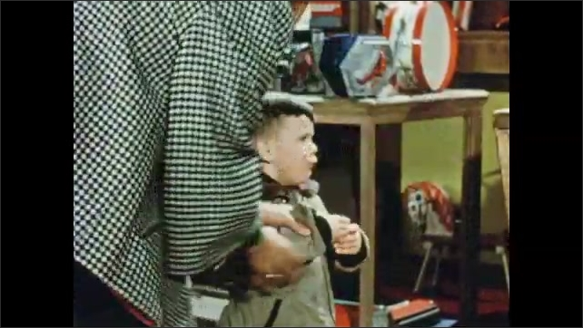 1950s: Yellow spot on hood of toy truck in toy store. Boy reaches up to grab toy truck on display but woman stops him and puts truck back. Girl picks up toy truck, shakes head and puts it back.