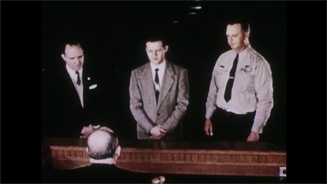 1950s: Courtroom, two men in suits stand with officer in front of judge. Judge sits in front of U.S. flag. Gavel hammers.