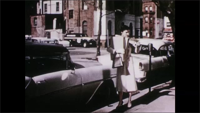 1950s: Police officer stands by car. City street, woman carrying boxes pulls ticket off windshield of car. One hour parking sign. Woman looks at watch, parking meter.