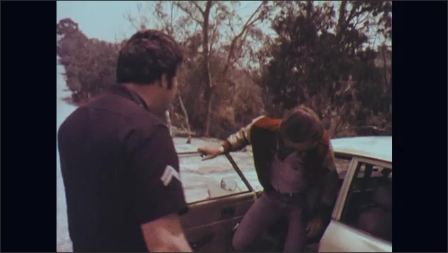 1970s: Two police officers get out of car on side of road and approach car they pulled over. Driver of car gets out and talks to police officer.