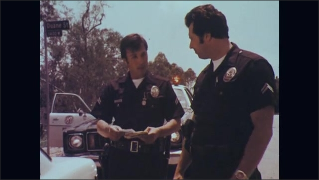 1970s: Police officer stands talking to driver of car next to car. Driver of car talks. Police officer approaches officer and hands him identification. Officer takes IDs back to car. Officer talks.