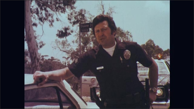 1970s: Driver of car stands next to car listening to police officer talk. Officer stands next to car talking. Driver listens. Officer talks. Driver talks then sits in car.