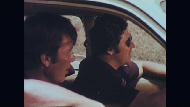 1970s: Car drives passed stop sign without stopping. Two police officers in car watch then talk. Car drives passed police. Police follow in pursuit.