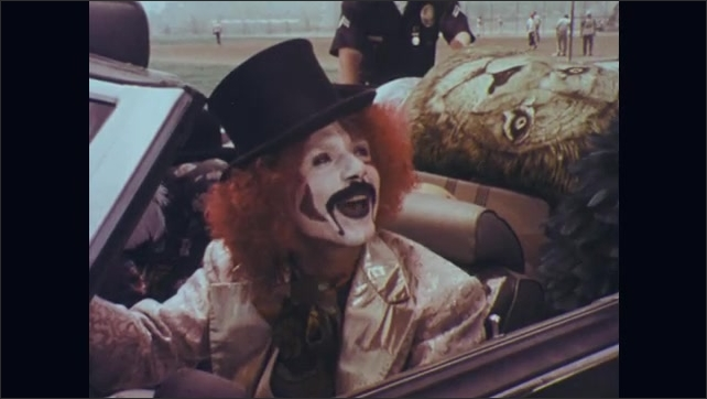 1970s: Two police officers approach pulled over car with man in face paint behind wheel. Police talk to driver. Driver in face paint talks. Officer talks. Other officer talks.