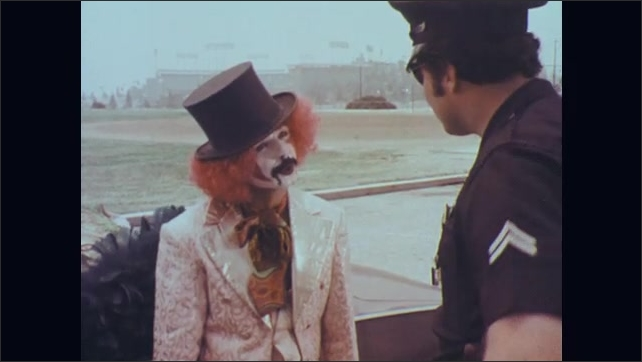 1970s: Police officer stands next to car holding joints in hand. Officer talks to man in face paint standing next to car. Officer puts handcuffs on man in face paint.