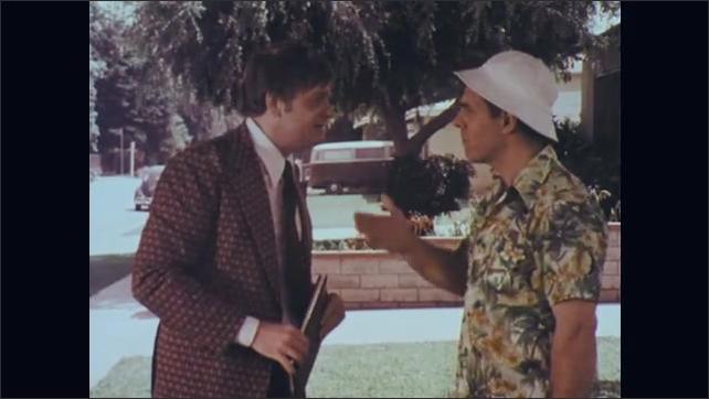 1970s: Man in gardening attire talks on lawn to man in suit. Men shake hands. Man in suit leaves.