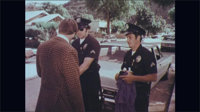 1970s: Two police officers talk to man standing next to car. Officer touches man's jacket while talking. Officers place man under arrest.