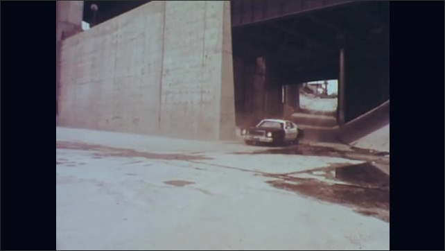1970s: Car drives onto empty water aqueduct. Police car follows in pursuit. Car drives fast down aqueduct.