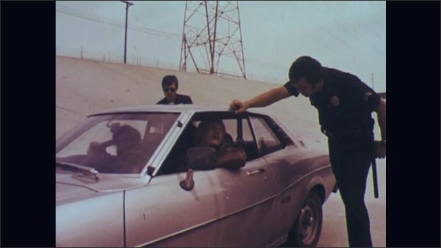 1970s: Police officer talks to man sitting in driver's seat of car. Man and woman in car listen to officer. Two officers stand on either side of car as officer talks to driver. Officer talks.