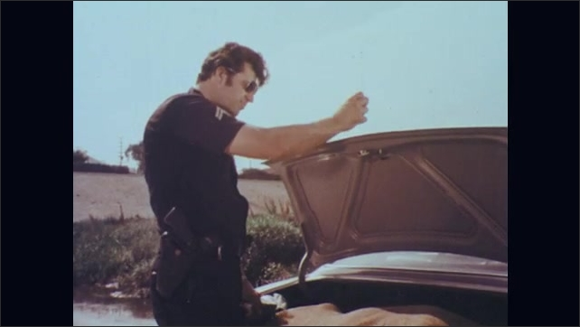 1970s: Man and woman stand next to police officer. Officer stands next to car trunk holding bag. Woman talks. Officer shuts trunk. Woman talks.