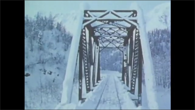1970s: Vehicle drives through snow. Dogs pull musher through snow.