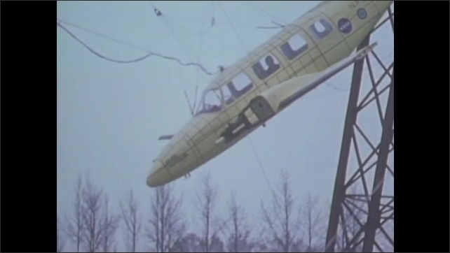 1970s: Plane is pulled upward with grid in background and pauses mid-air. Plane releases, swings forward, and crashes into the ground.