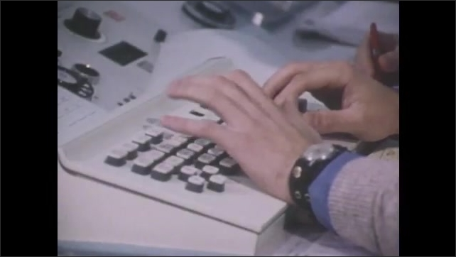 1970s: Men work in office, answer phones, and type on computers.