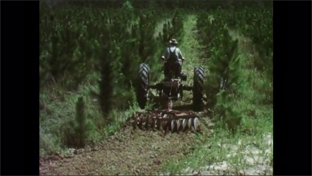 1950s: Man drives tractor through field.