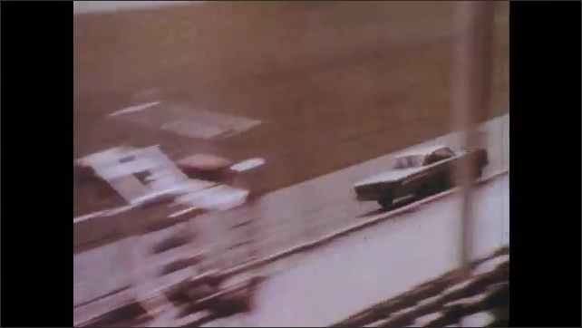 1960s: UNITED STATES: car passes empty grandstand. Cars on race track