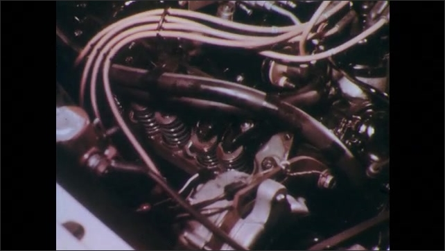 1960s: UNITED STATES: flag flies at speedway track. NASCAR flag. World Record attempt. Close up of car engine. Man works under car.