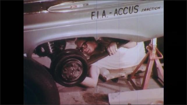 1960s: UNITED STATES: mechanic works underneath race car. Man fixes wheels on race car. Roll bars on car. Men work on engine