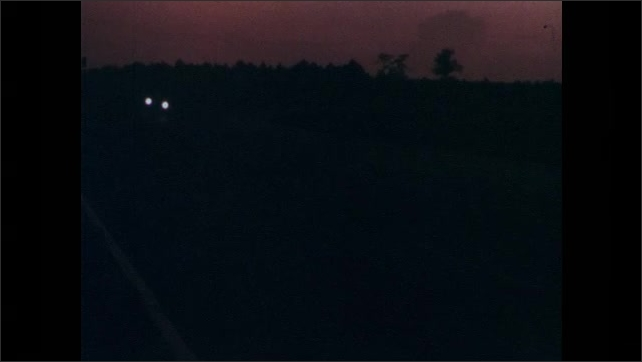 1960s: UNITED STATES: speedway race track in dark. Dawn over speedway track. Car lights on track. Cars drive around track