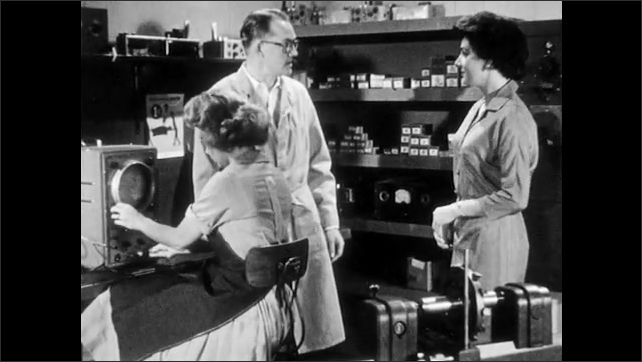 1950s: Woman sits in lab, chews gum, man stands, reaches over her to twist knobs on oscilloscope. Second woman walks in confidently, hands man a letter.
