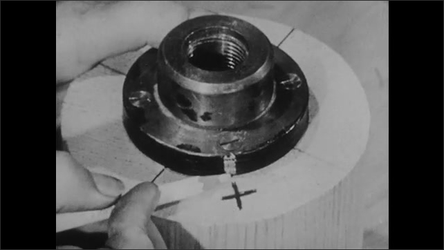 1940s: Close up, pencil marks on metal face plate. High angle, man puts part in lathe machine. Close up, machine part moves.